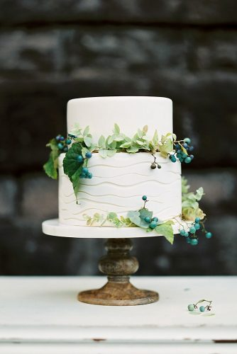 small rustic wedding cakes white cake on a wooden stand with structural waves decorated with greens and blue berries carlos hernández photography