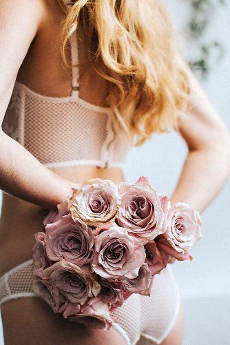 wedding boudoir book bride in white lingerie holds behind her pink flowers hazelwood photo