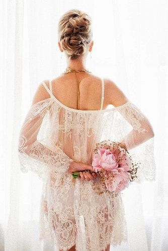 wedding boudoir book bride with updo in white lace holds a rose bouquet bridalboudoir via instagram