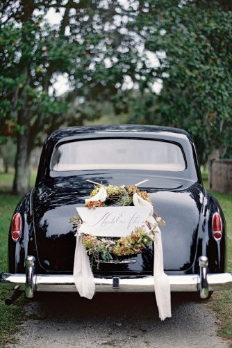 wedding car decorations a black car is decorated with a wreath of greens and a romantic inscription jose villa photography