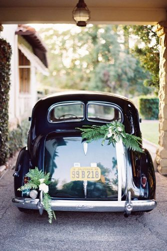wedding car decorations a black car is decorated with greenery and white roses jose villa photography