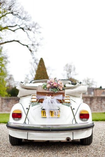 wedding car decorations on the trunk of the car a wicker basket with flowers and a light cloth amanda drost