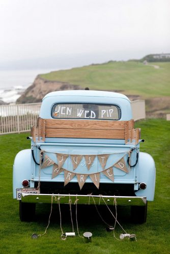 wedding car decorations pickup is decorated with a garland of burlap and cans larissa cleveland photography