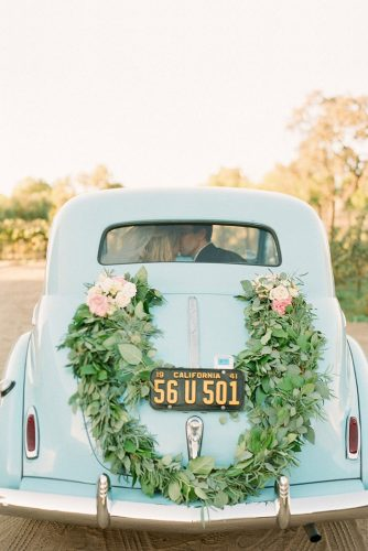 wedding car decorations retro decorated with greenery and pink roses bride and groom kisses inside caroline yoon fine art photography