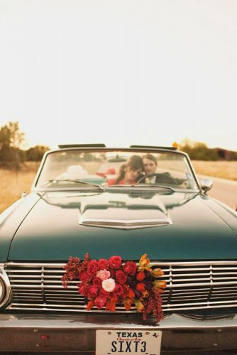 wedding car decorations the bride and groom ride in a car decorated with red roses the life you love photography