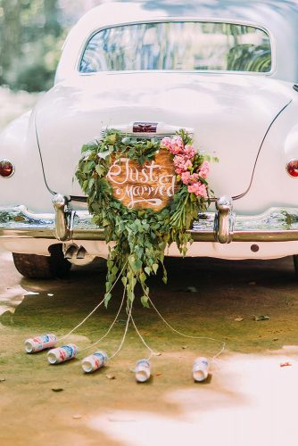 wedding car decorations with a wooden board just married and greens and tin cans weddingcom via instagram
