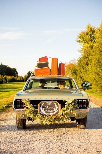 wedding car decorations with greenery and an inscription on the roof of the trunk with suitcases amanda hein photography