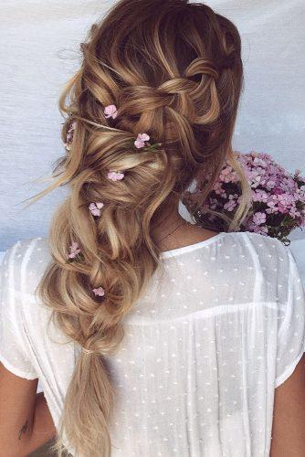 wedding hairstyles with flowers messy braided hairdo with small lilac flowers emma chen via instagram