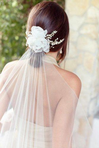 wedding hairstyles with veil low updo with white flower and veil on brown hair jonidaripani