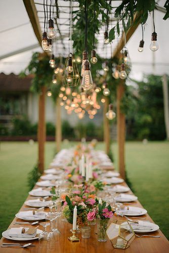 wedding light long decorated with flowers and candles over a table light bulb bali wedding photographer via instagram
