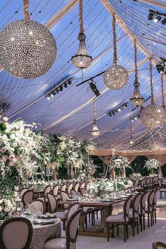 wedding light luxurious reception under a transparent awning with shiny chandeliers jessica claire via instagram