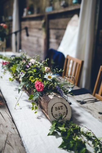 wedding table decorations wooden stump with greenery and wildflower photography34