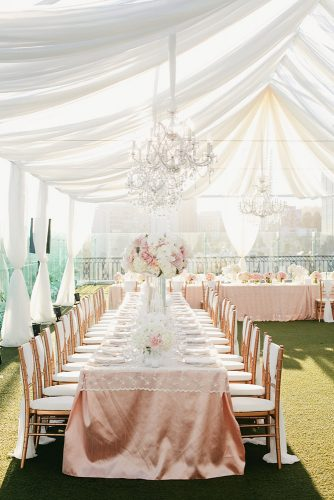 wedding tent on a green lawn under a white awning with chandeliers rosy wedding tables onelove photography