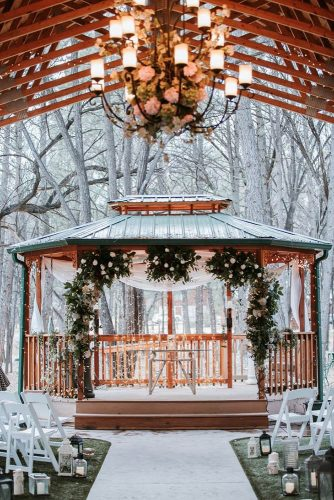 winter wedding decorations the ceremony in the gazebo is decorated with lanterns of greenery with white flowers and light fabrics emily joanne wedding films and photography