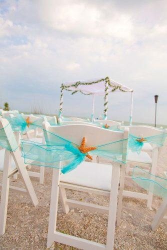beach wedding decoration ideas starfish and blue ribbon on guest chairs scott kelsey photography