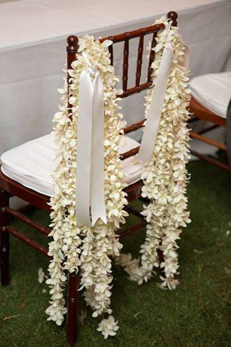 beach wedding decoration ideas tropical flower garland and ribbons decorate chair meg baisden photography