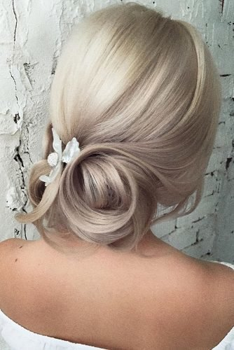 bridesmaid updos elegant simple low updo on blonde hair with white pin flower accessory olesya_zemskova