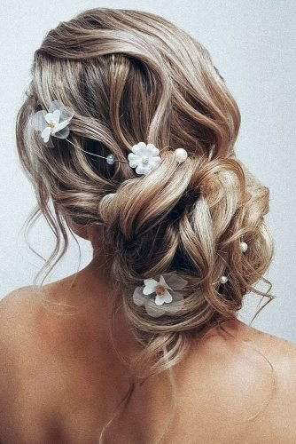 bridesmaid updos volume low bun with curls and white flowers hairbyhannahtaylor