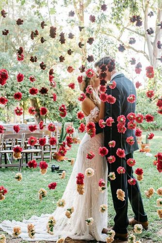 cheap wedding decorations wall of red flowers behind which the kiss of the bride and groom cara robbins studio