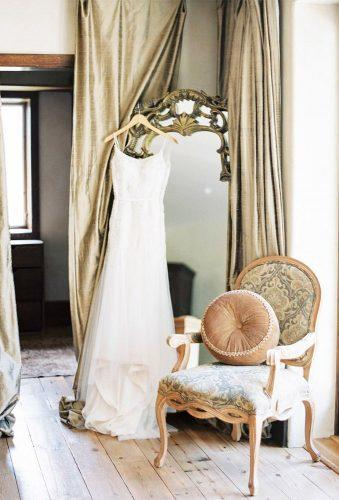 hanging wedding dress dress om mirror near chair codyhunterphotography