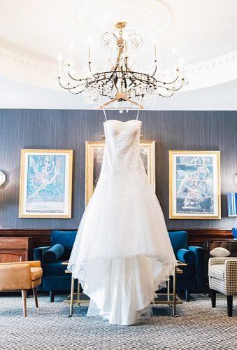 hanging wedding dress dress on chandelier heathereastphoto