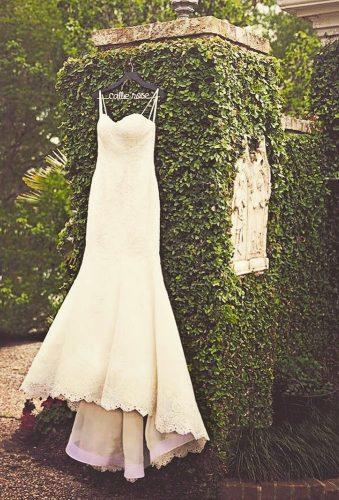 hanging wedding dress dress on greet wall sallyveephotography