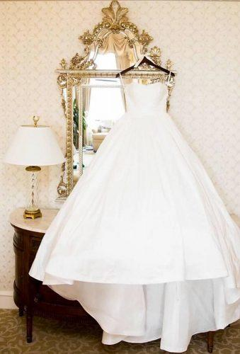 hanging wedding dress dress on the morror cristinagphoto