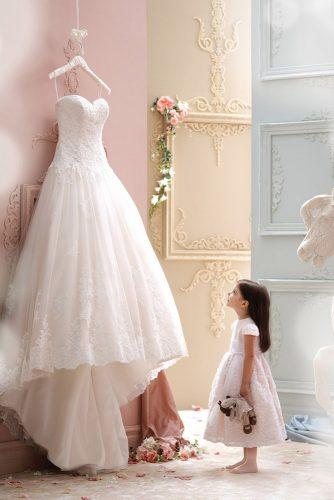 hanging wedding dress little girl look at dress moncheribridals