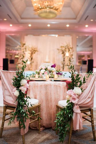 rose gold wedding décor on reception the table of the bride and groom with a shiny tablecloth with golden chairs decorated with pink cloth and roses becky's brides via instagram