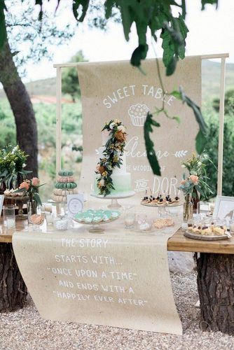 rustic backyard wedding decoration dessert table is decorated with an inscription and a green one based on wooden stumps sandy and odysseas