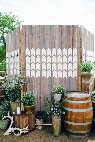 rustic backyard wedding decoration escort card display on a wooden fence flowers in barrels and buckets the nichols via instagram