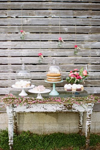 rustic backyard wedding decoration old dessert table decorated with flowers on a background of flowers in glass jars lauren fair photography