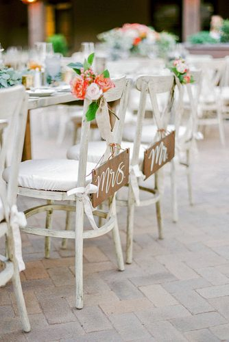 rustic backyard wedding decoration white wooden furniture chairs decorated with flowers and inscriptions rachel solomon photography