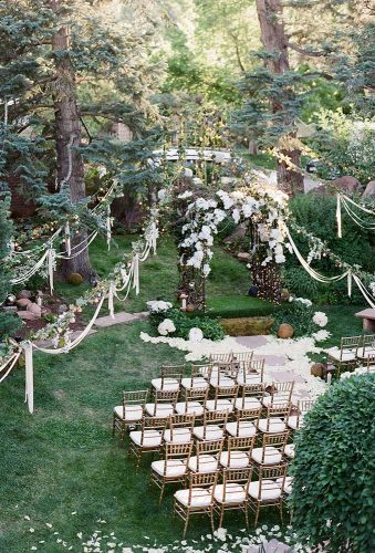 rustic backyard wedding decoration whitewashing ceremony with a lush arch of white flowers and ribbons jenna walker photography