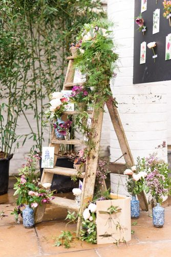 rustic backyard wedding decoration wooden ladder decoration with moss and flowers in blue vases anushé low