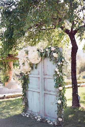 rustic backyard wedding decoration wooden old blue door backdrop decorated with green and white flowers clayton austin