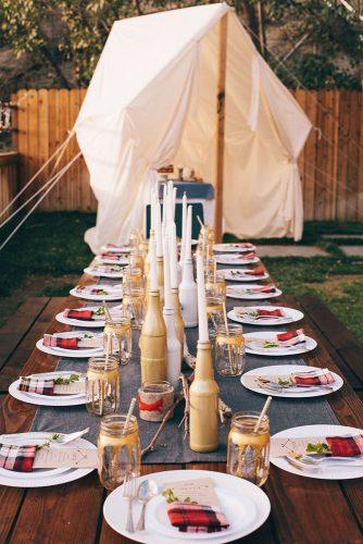 rustic barbecue bbq wedding a long wooden table with gold bottles of candlesticks white plates and red checkered napkins steve steinhardt