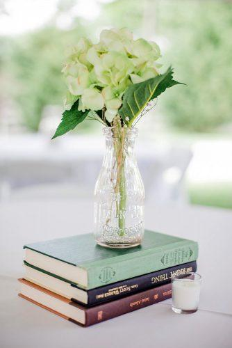 rustic wedding decor centerpiece with books and flower in glass jennifer thornhill photography