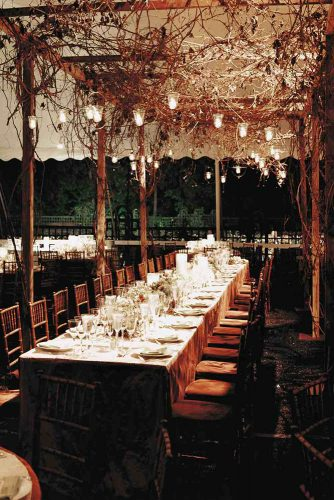rustic wedding reception a table under the tent decorated with brunches and suspended candles christian oth studio