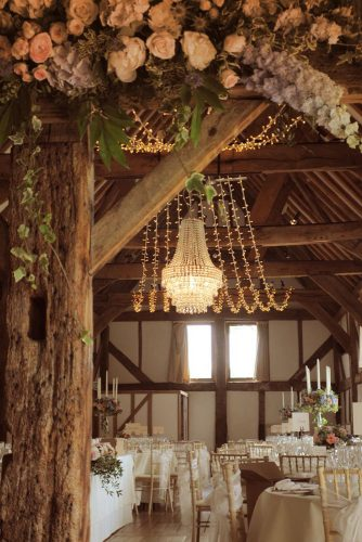 rustic wedding reception glam in wooden barn decorated with roses elegant chandelier and lights oakwood events
