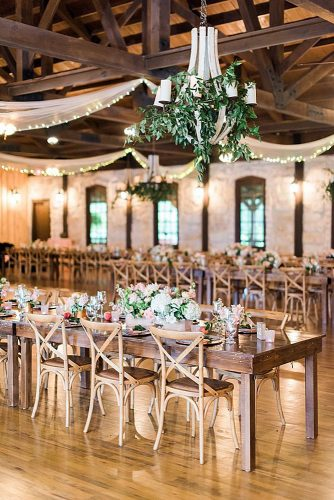 rustic wedding reception in barn a wooden table with a flowery hall is decorated with a white cloth dana fernandez photography