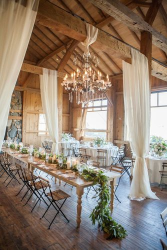rustic wedding reception in barn decorated with a white cloth and an elegant chandelier on the table greens rgv photographer