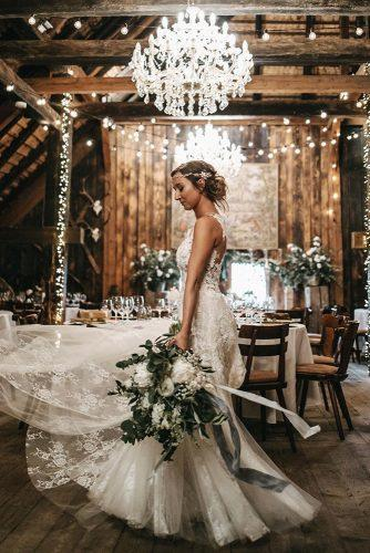 rustic wedding reception in the barn elegant wth chandelier with grenery and light bulbs nadja_osieka_hochzeitsfotograf