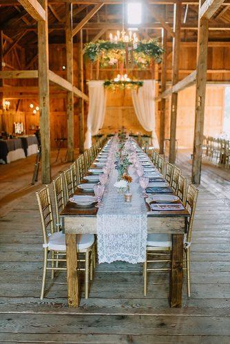 rustic wedding reception in the barn with long lace tablerunner and pink glasses darling photo