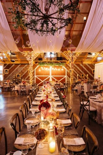 rustic wedding reception in wooden barn white cloth greenery and light bulbs karlisch photography