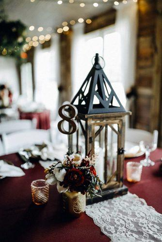 rustic wedding reception lantern centerpiece with tablenumber ob dark red tablecloth rad red creative