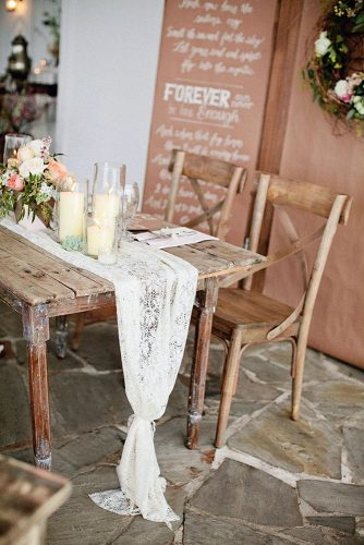 rustic wedding reception old wooden table decorated with white lace flowers and candles kristyn hogan via instagram