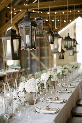 rustic wedding reception over a table with a white tablecloth and flowers hanging lanterns elizabeth anne designs