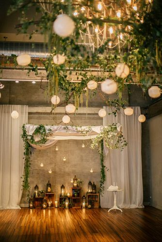 rustic wedding reception photo backdrop decorated with lanterns and wooden boxes under the ceiling greens emily wren photography
