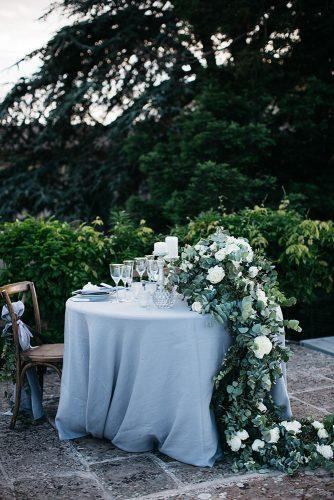 rustic wedding reception round sweetheart table with grey tablecloth with greenery stefano santucci studio